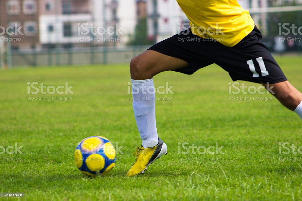 Low section of soccer player carrying ball in soccer field stock photo