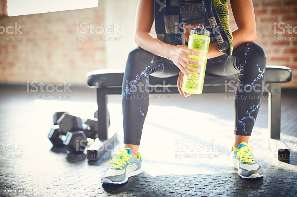 Low section of tired woman holding water bottle stock photo