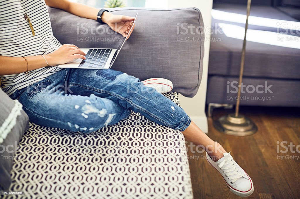 Low section of trendy blogger using laptop on window seat stock photo