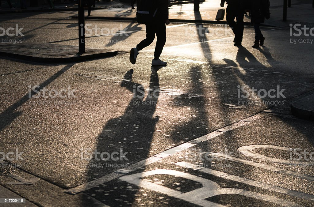 Low section of two people crossing the road stock photo