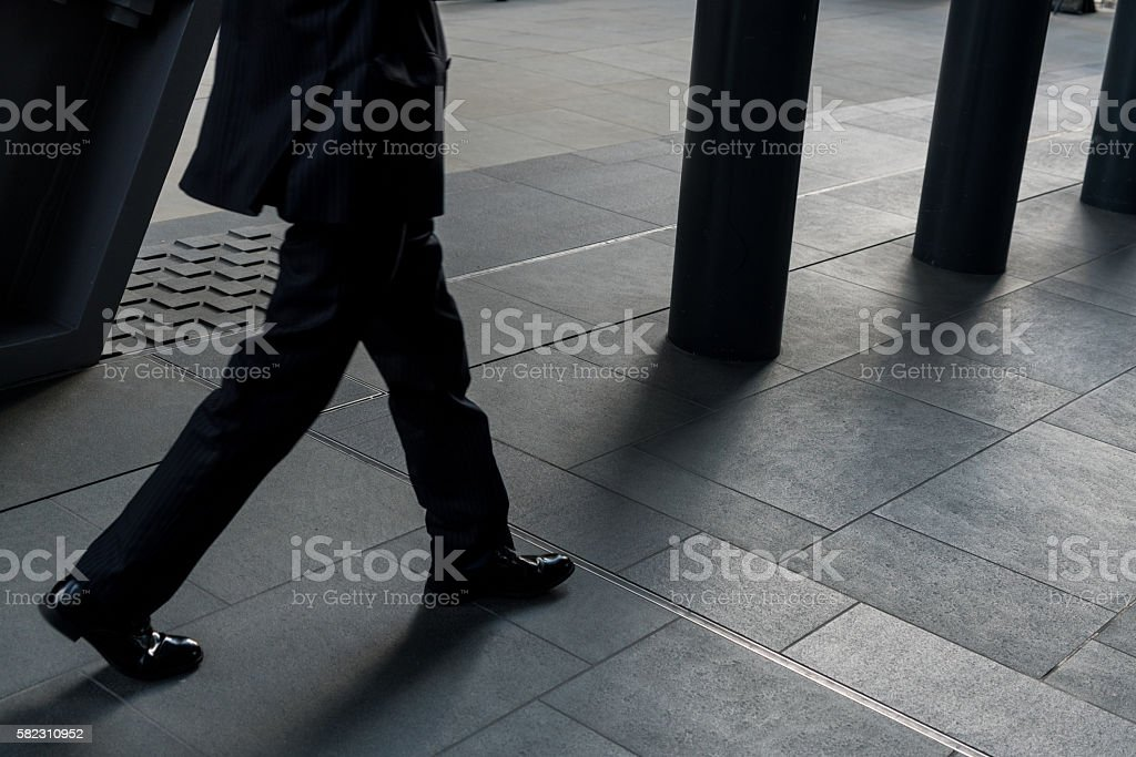 Low section of unrecognizable person crossing the walkway in city of...