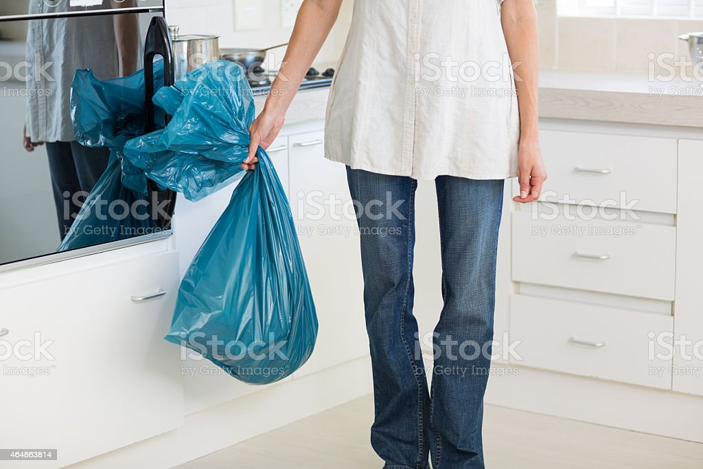 Low section of woman carrying garbage bag in kitchen stock photo