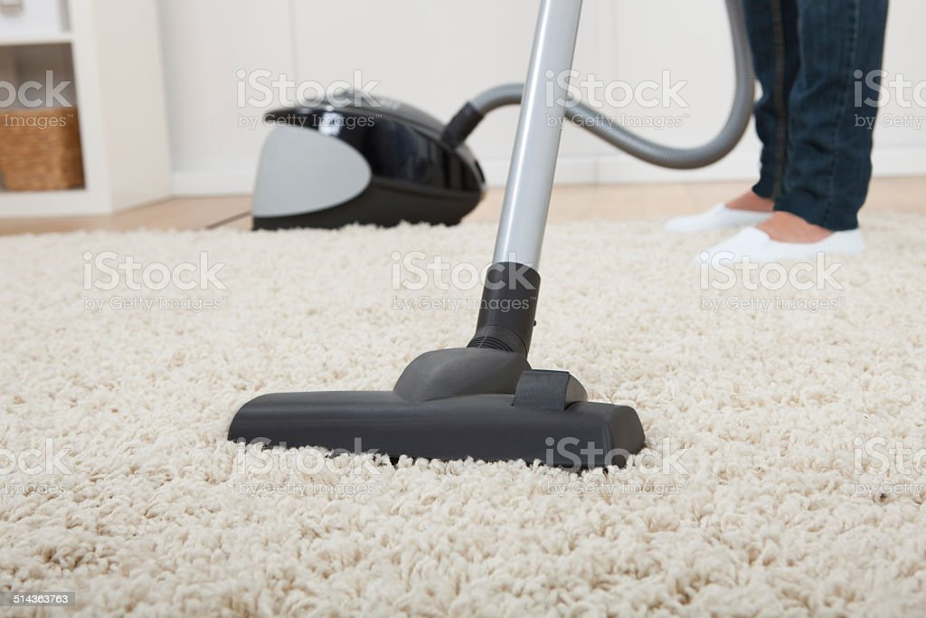 Low Section Of Woman Vacuuming Floor stock photo