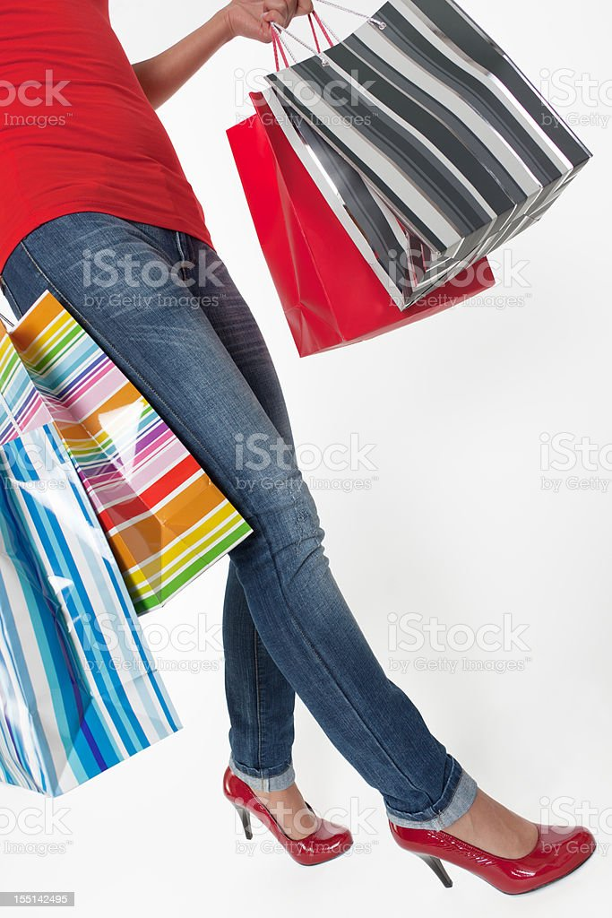 Low section of young woman with multi colored shopping bags royalty-free stock photo
