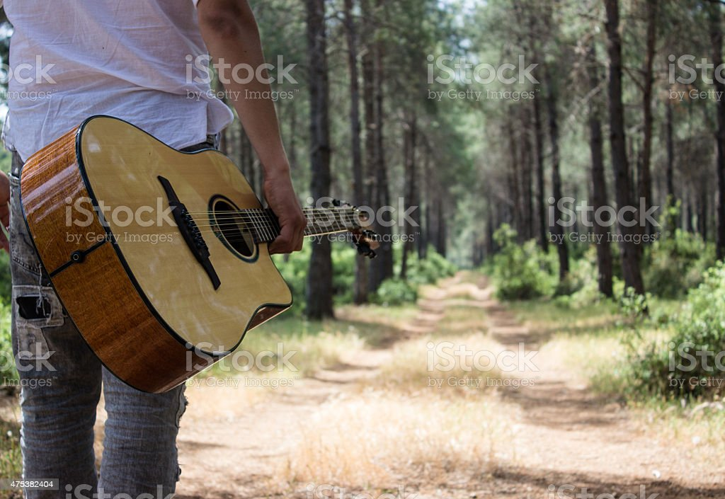 Low section view of guitarist walking on woodland stock photo