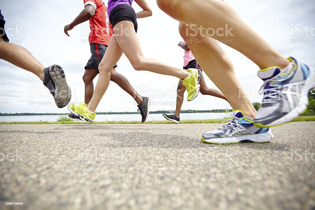 Low side view of athletes running on a track stock photo
