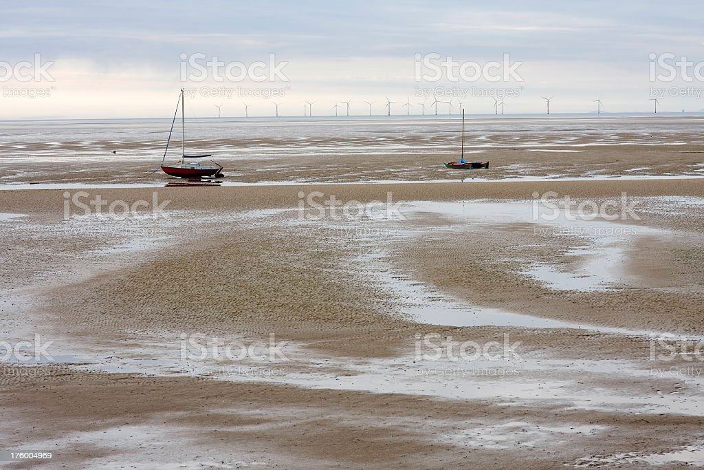 'Low tide, small boats, wind turbines' stock photo