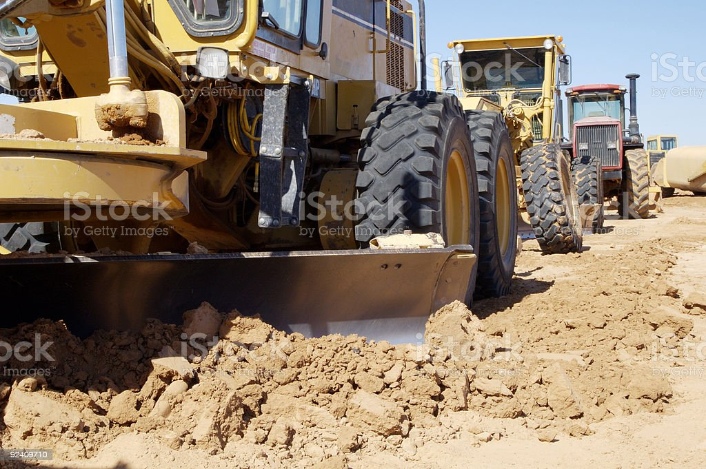 Low view of a large grader grading dirt with other machines stock photo