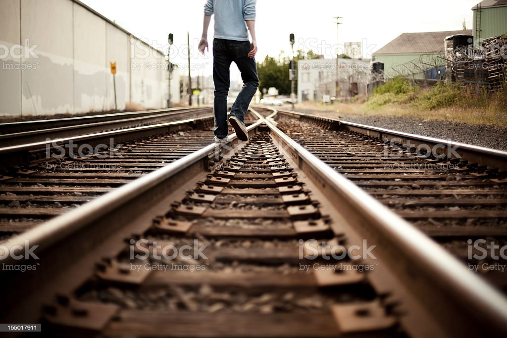 Low view of a male figure walking down some train tracks royalty-free stock photo