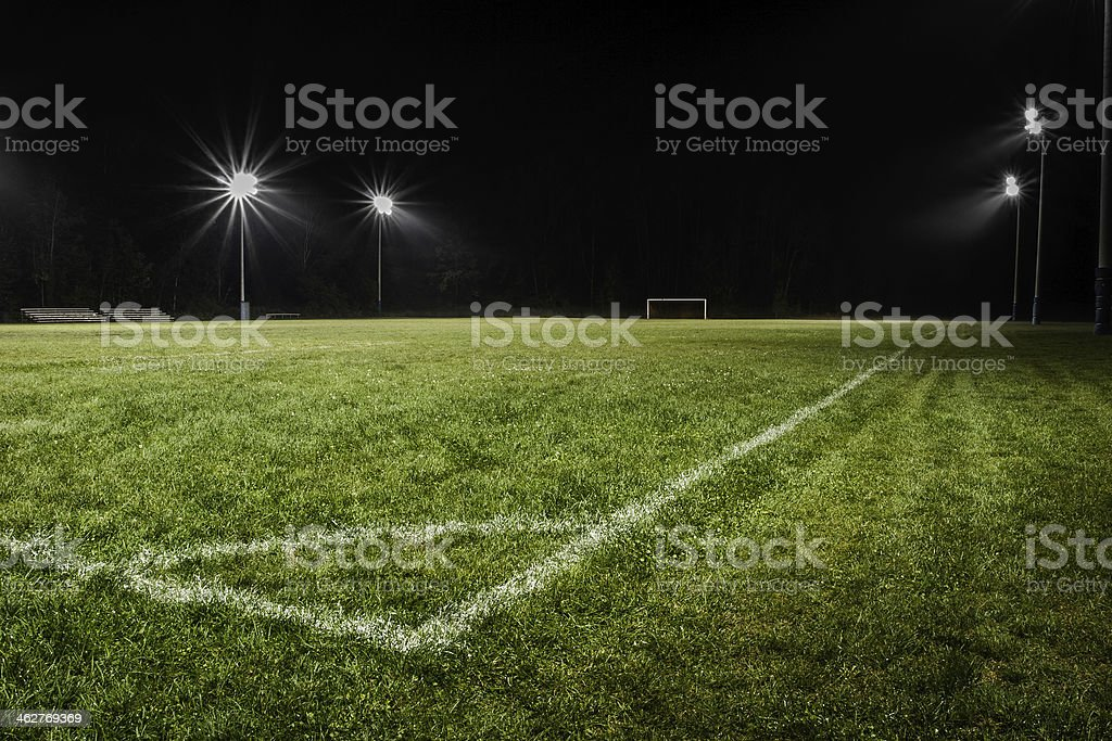 Low view of empty soccer field at night with stadium lights. royalty-free stock photo