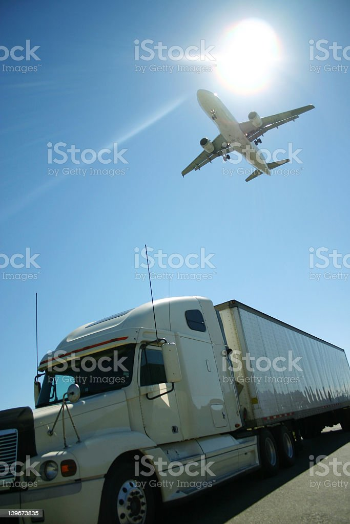 Low view of the underside of an airplane flying over truck royalty-free stock photo
