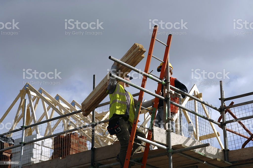 Low view of two construction workers on top of house frame stock photo