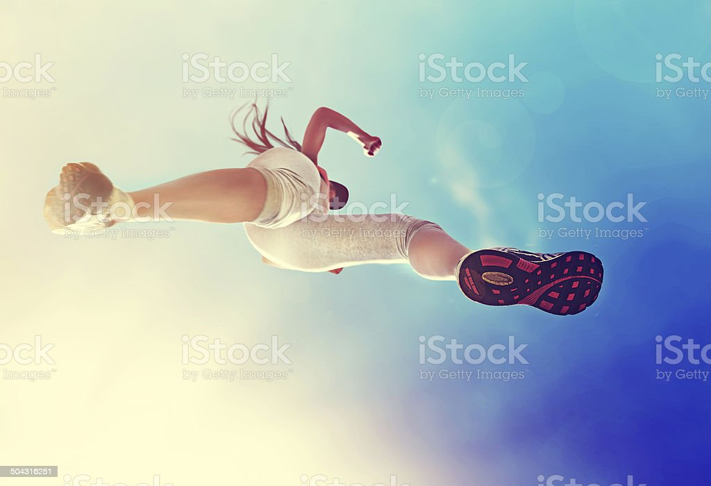 Low-angle shot of a woman running over a puddle stock photo