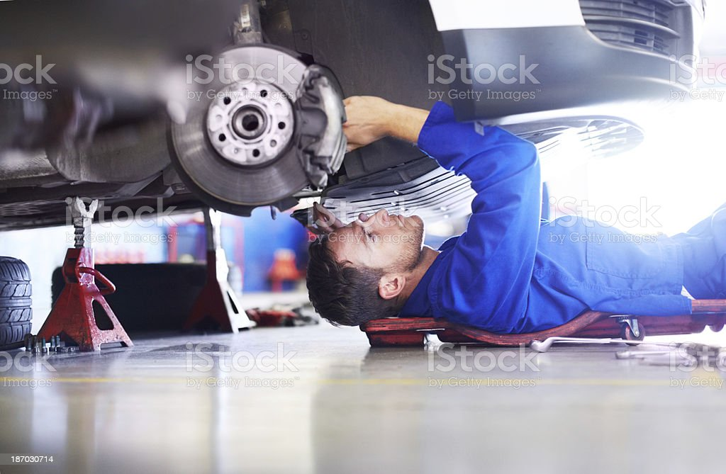 Low-angle shot of mechanic working under a car stock photo
