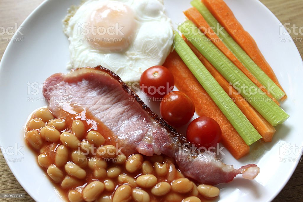 Low-calorie, healthy fried breakfast, bacon, poached-egg, raw vegetables, tomatoes, baked-beans royalty-free stock photo