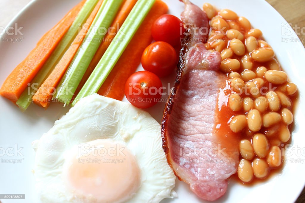 Low-calorie, healthy fried-breakfast, bacon, poached egg, raw vegetables, tomatoes, baked-beans stock photo