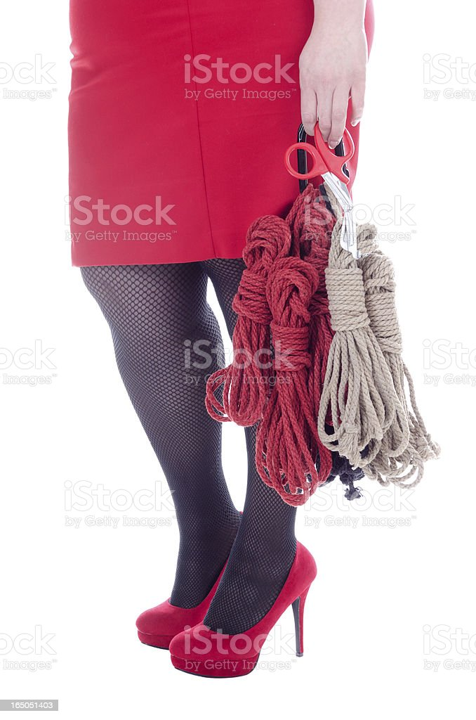 Lower body of woman carrying bondage rope and shears. stock photo