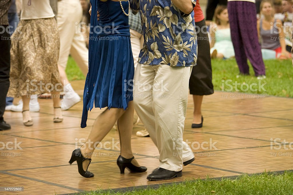 Lower body shot of elderly couples dancing in a park setting stock photo