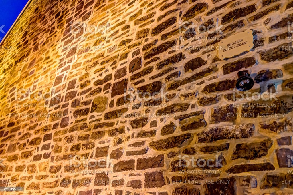 Lower old town street with closeup of Rue Cul-De-Sac sign on stone wall at night stock photo