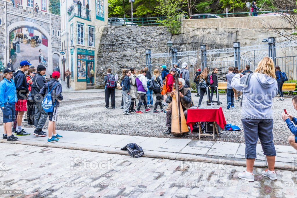 Lower old town street with Parc de la Cetiere and people listening to harpist play stock photo