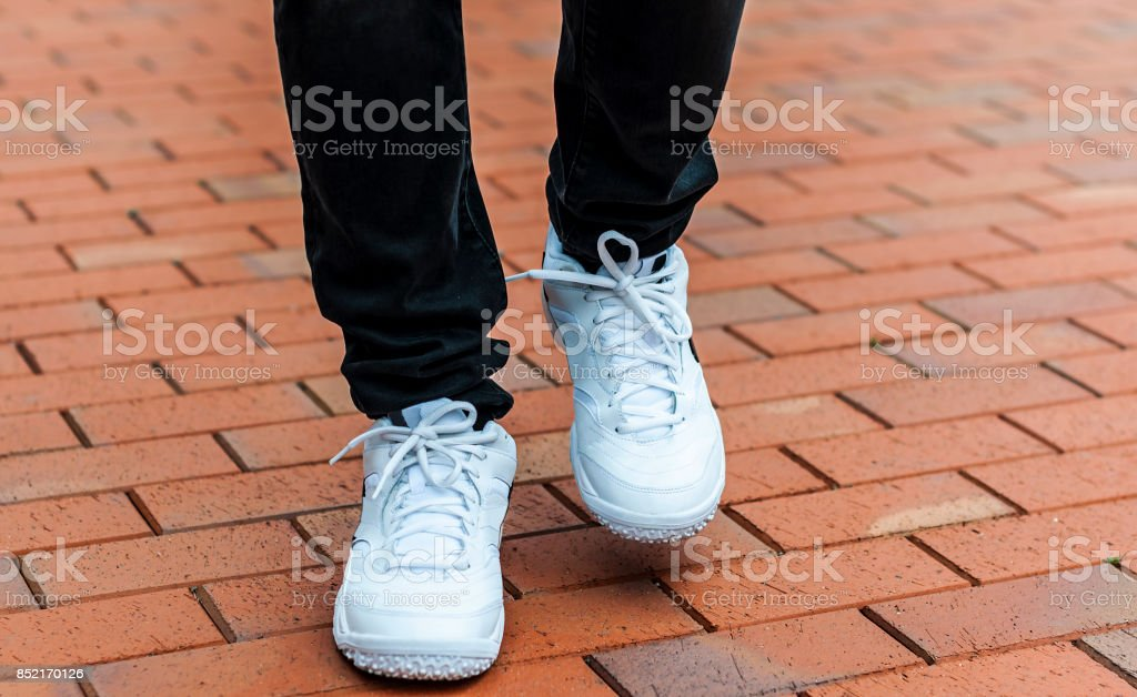 lower part of the male legs in white sneakers stock photo