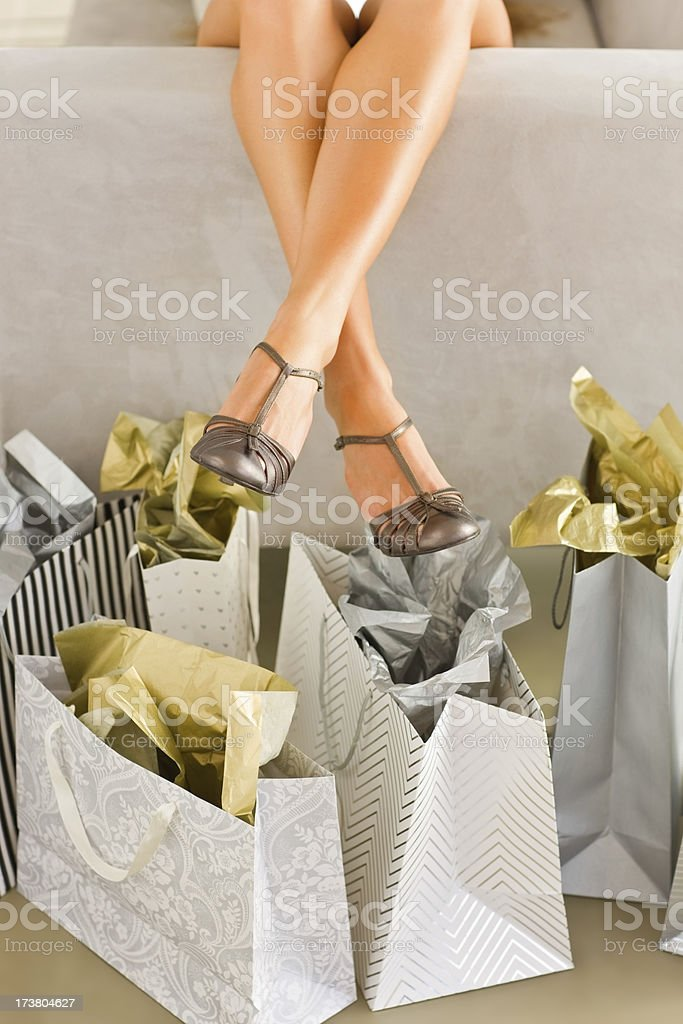Lower section of young woman legs with shopping bags royalty-free stock photo