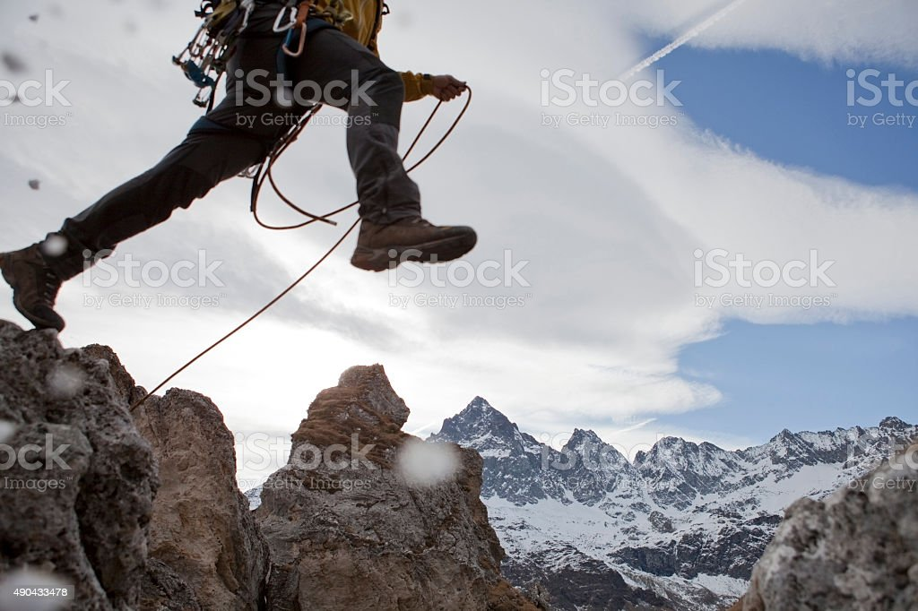 Lower torso of mountaineer in mid-air jump stock photo
