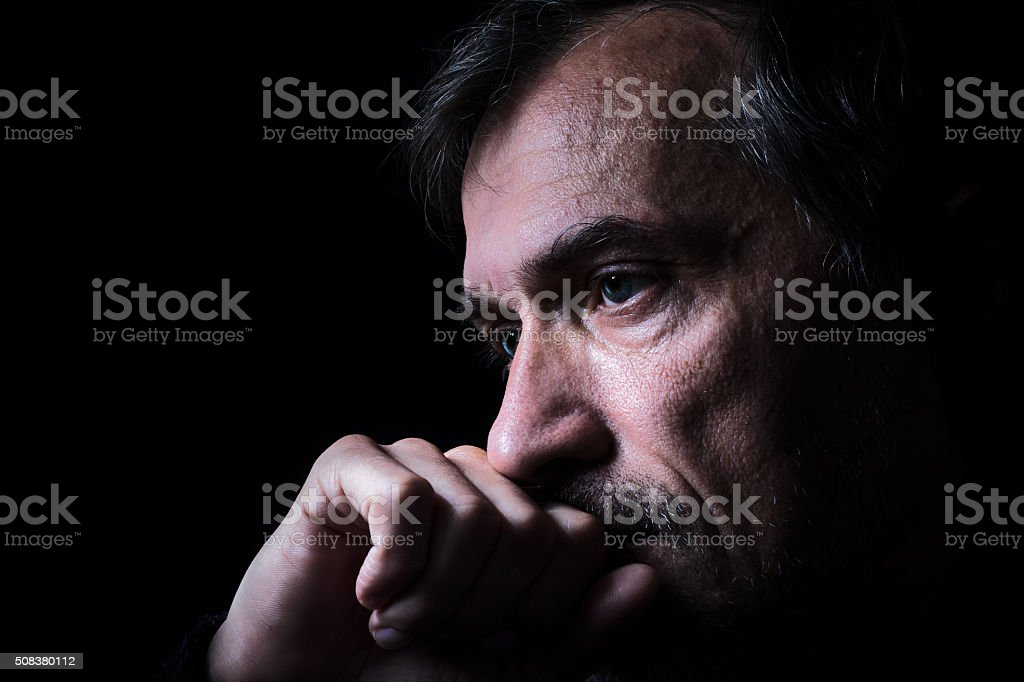 Low-key old man closeup portrait with black background stock photo