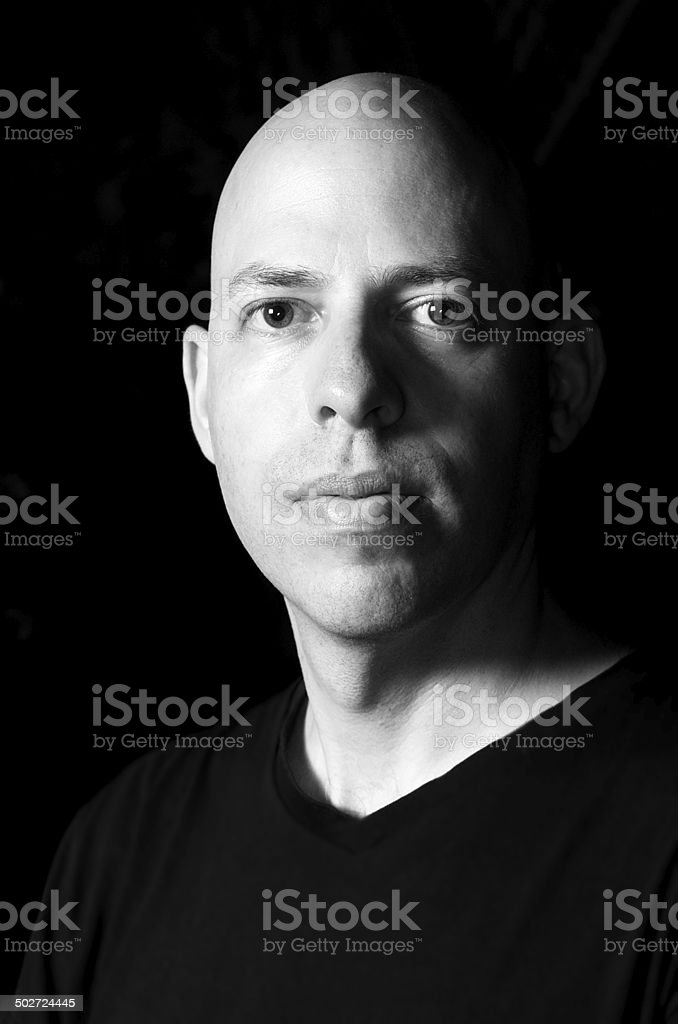 Low-key portrait of a man in black and white stock photo