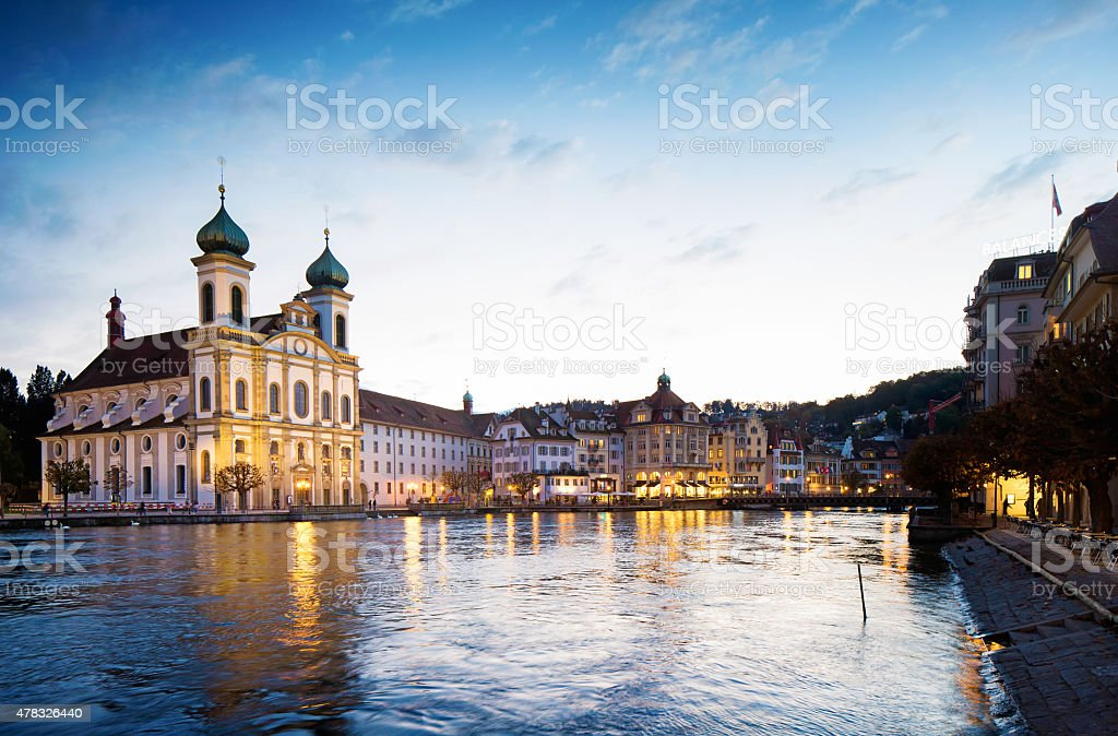 Lucerne Switzerland Reuss river south shore sunset with Jesuit Church stock photo