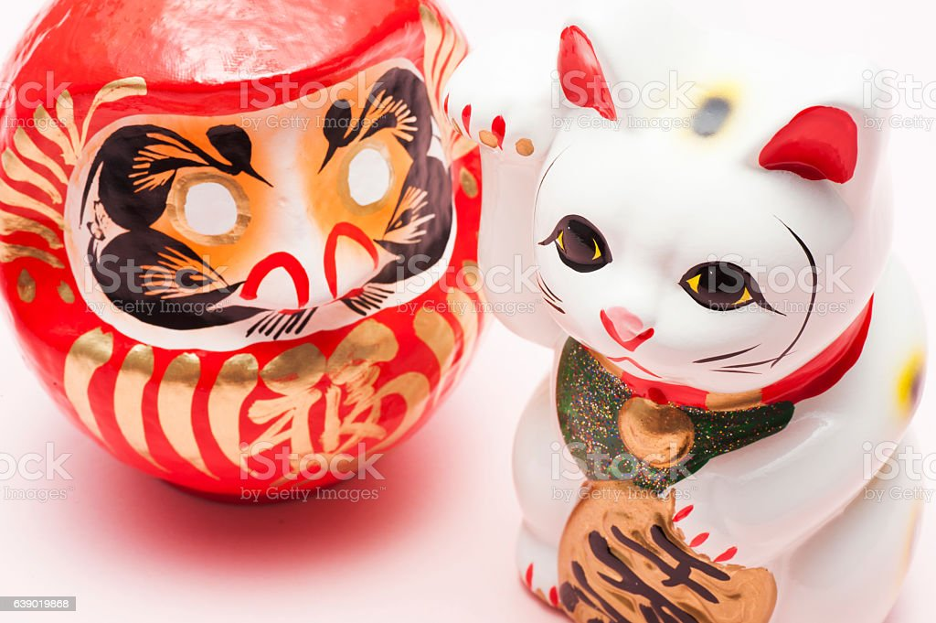 lucky cat and dharma on pink background stock photo