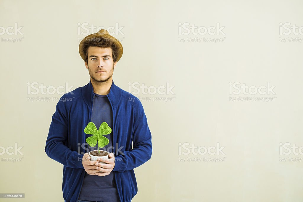 Lucky hipster holding four leave clover stock photo