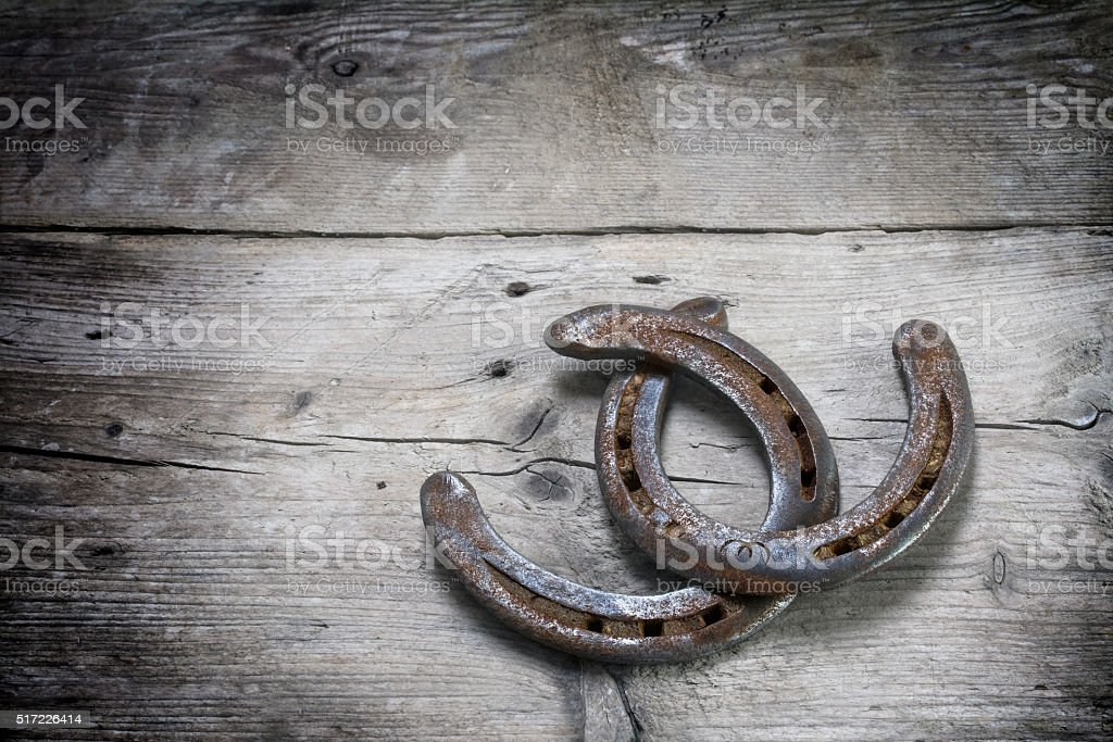 lucky horseshoes with rust intertwined on rustic wooden planks stock photo