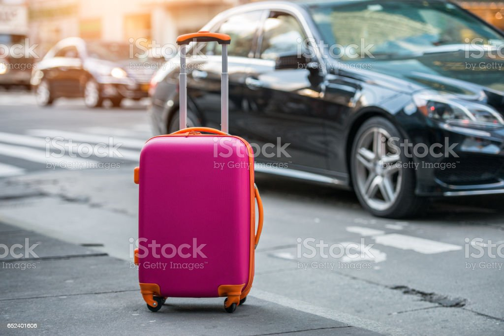 Luggage bag on city street to pick up taxi car stock photo
