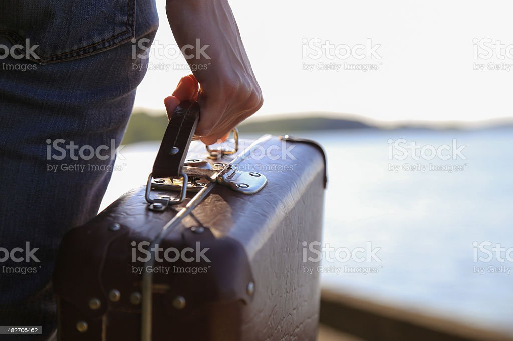 luggage in a female hand on a background of the sea stock photo