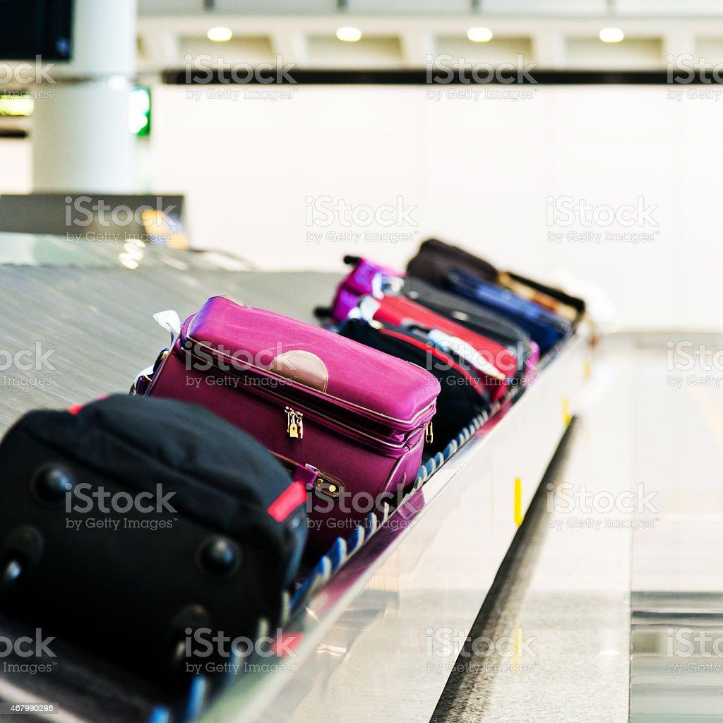 Luggage on belt at baggage claim stock photo