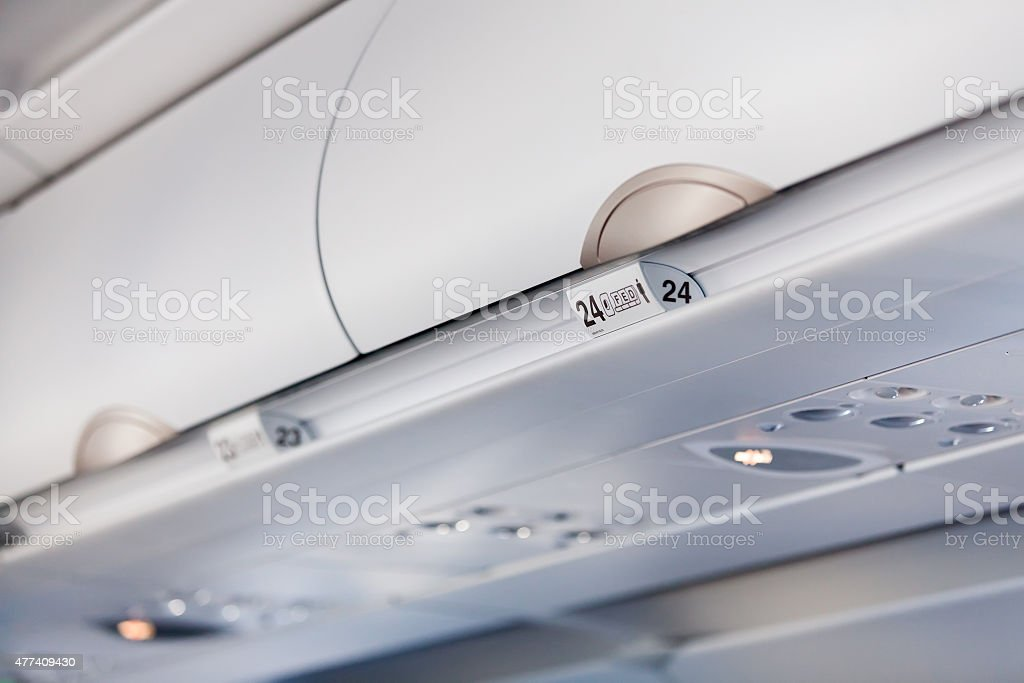 Luggage shells with seat numbers inside the passenger airplane stock photo