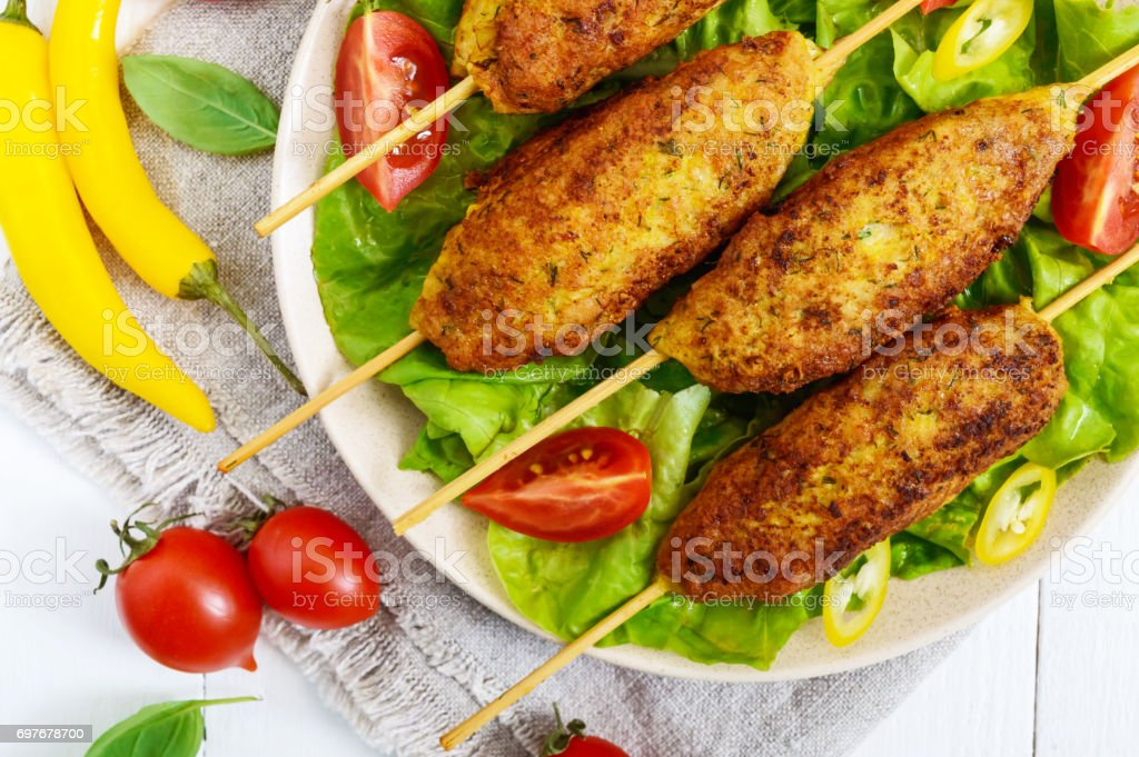 Lula-kebab is a meat dish, traditional for the Caucasus, in Central Asia and Turkey. Minced meat strung on a skewer and fried. Serve on a plate with lettuce leaves and fresh tomatoes. Close up stock photo