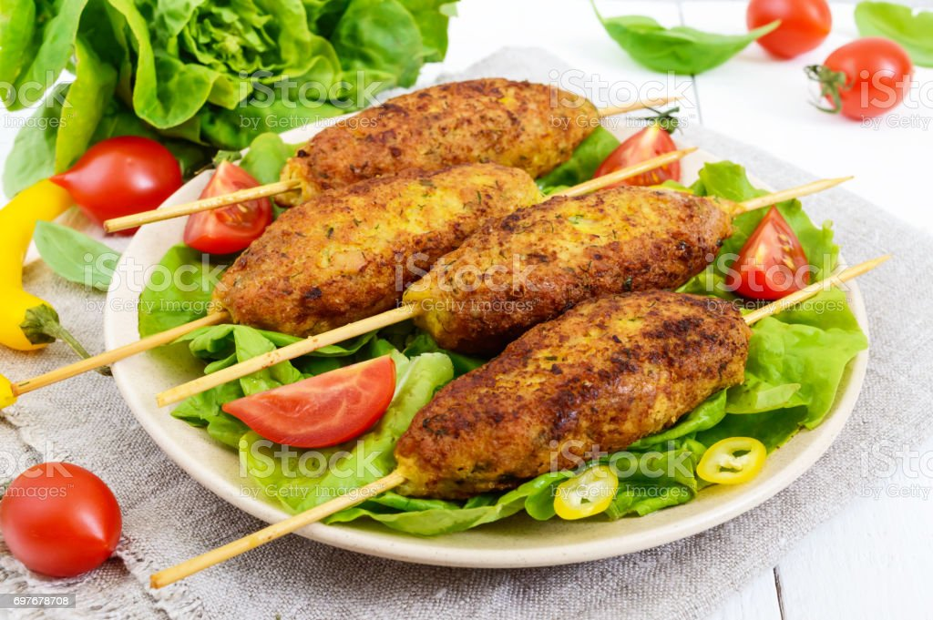 Lula-kebab is a meat dish, traditional for the Caucasus, in Central Asia and Turkey. Minced meat strung on a skewer and fried. Serve on a plate with lettuce leaves and fresh tomatoes. stock photo