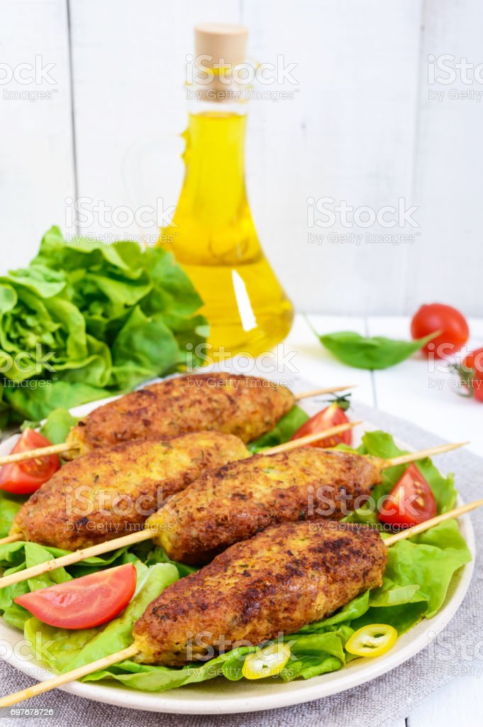 Lula-kebab is a meat dish, traditional for the Caucasus, in Central Asia and Turkey. Minced meat strung on a skewer and fried. Serve on a plate with lettuce leaves and fresh tomatoes. Vertical view stock photo