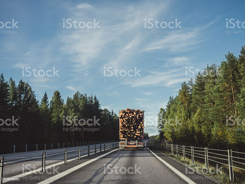 Lumber truck driving on highway stock photo
