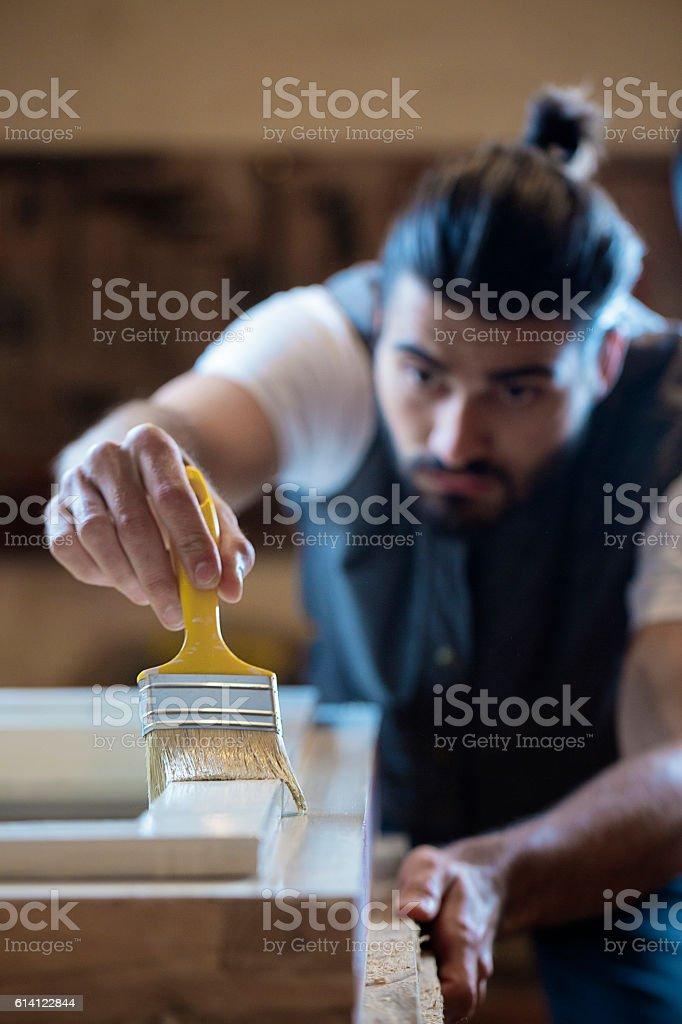 Lumberjack applying wood stain stock photo