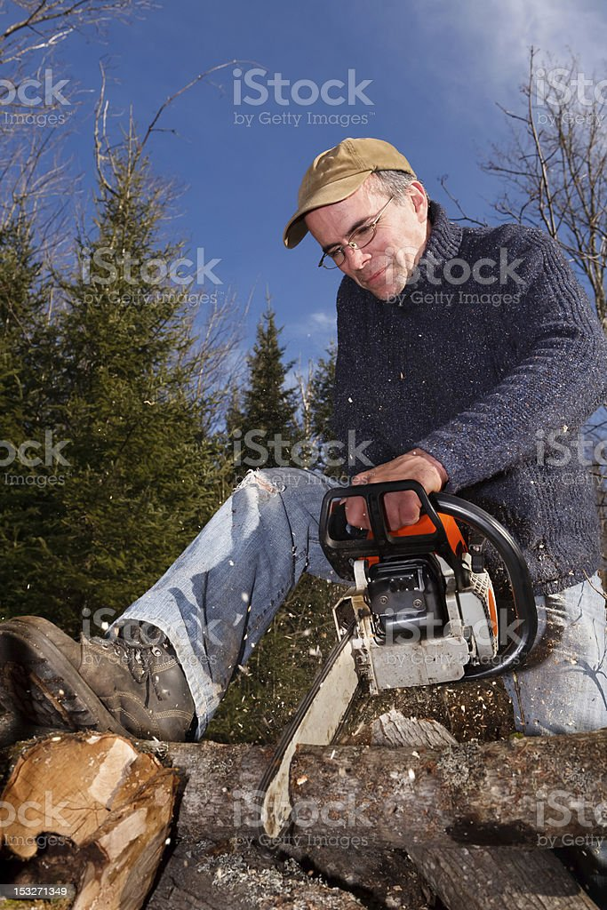 Lumberjack is using a chainsaw. stock photo