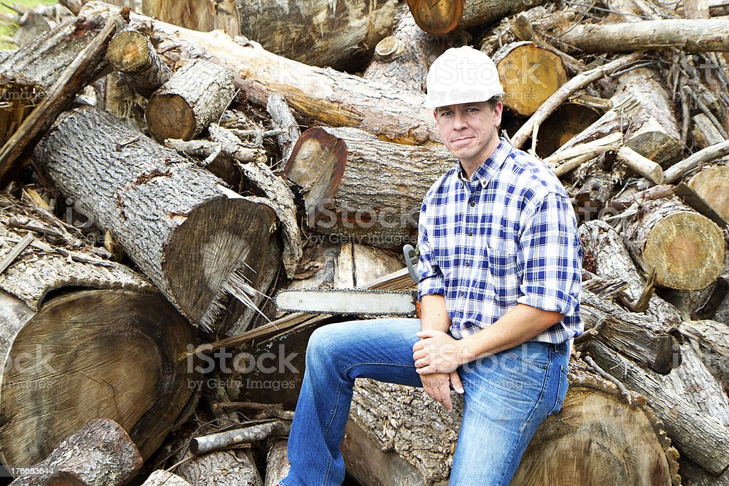 Lumberjack sits on log pile and looks at camera stock photo