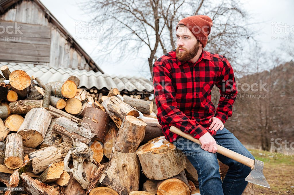 Lumberjack with axe resting outdoors stock photo