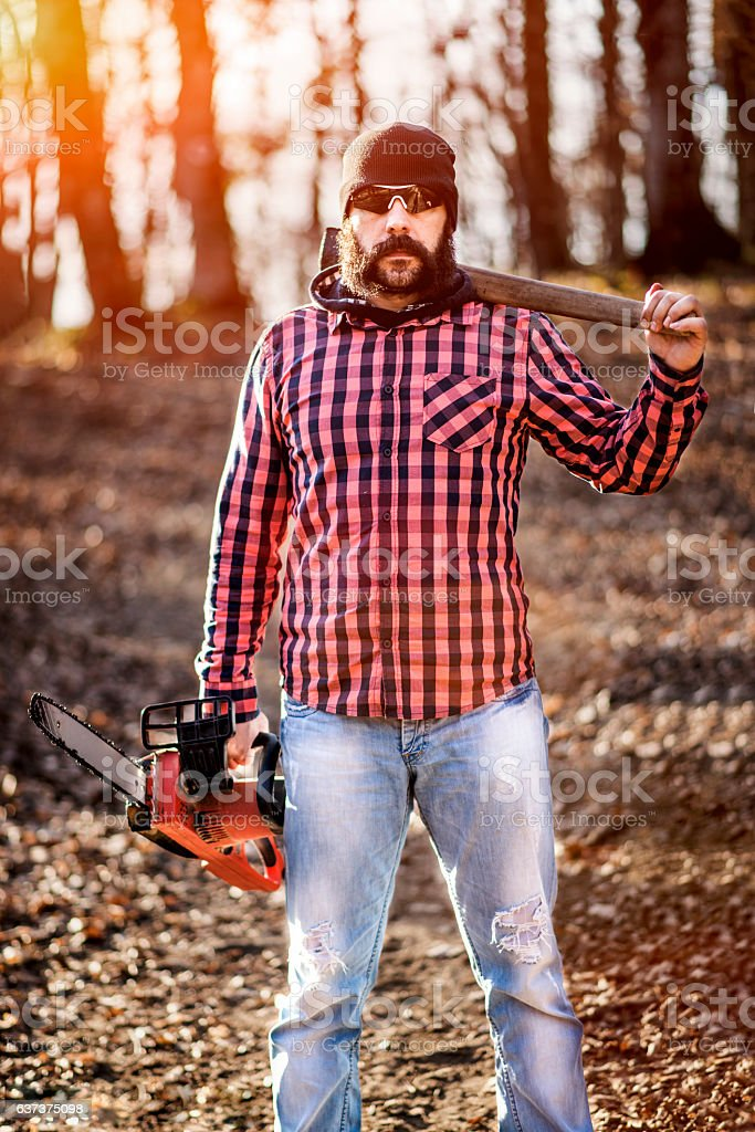Lumberjack worker standing in the forest with axe and chainsaw stock photo