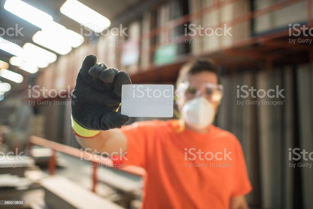 Lumberyard worker holding a business card stock photo