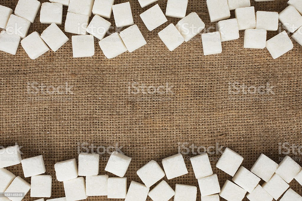 Lump sugar lying on burlap royalty-free stock photo