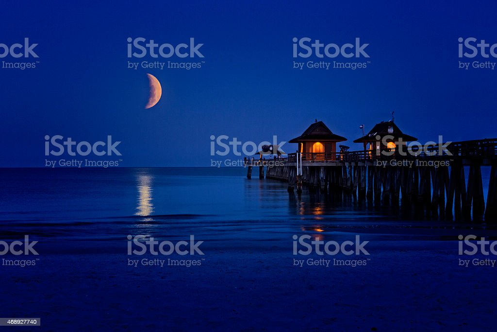 Lunar Eclipse Over the Naples Pier stock photo