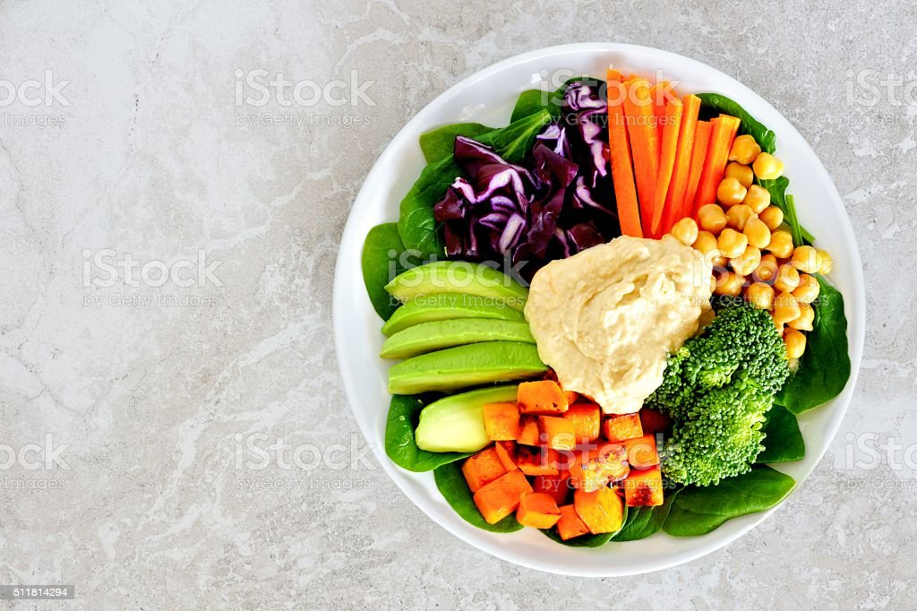 Lunch bowl with fresh vegetables and hummus on marble stock photo